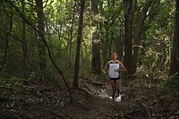 Mixed race woman running through forest