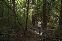 Mixed race woman running through forest