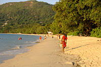 People walking along Beau Vallon beach, early evening light, Mahe, Seychelles, Indian Ocean