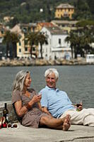 Senior couple drinking red wine by the water, Italy