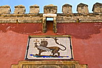 Royal lion emblem fresco and fortifications above entrance of the Alcazar, Seville, Andalusia, Spain, Europe