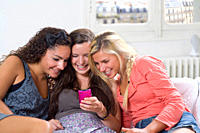Young women share phone text on couch