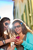 Young women share cell phone in street