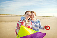 Two girls holding kite on beach