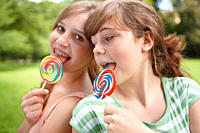 2 girls eating lollipops together