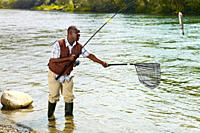 Black man with net catching fish in stream