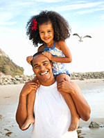 Black father carrying daughter on shoulders on beach