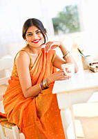 Mixed race woman in traditional Indian clothing drinking coffee