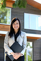 Mixed race real estate agent standing near house