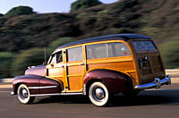 Car, Oldsmobile 68 Station Wagon, Woody, model year 1947, vintage car, 1940s, fourties, ruby colored, wood, sedan, driving, diagonal back, back view, ...