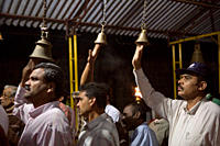 3 three middle aged Indian Hindu men chiming bells above their heads at night in a makeshift temple, Hutteri Harvest festival, Madikeri, Coorg / Kodag...