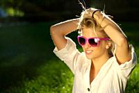 Attractive young blonde woman posing in nature with pink sunglasses
