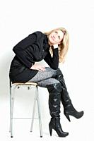 woman wearing fashionable black boots sitting on chair