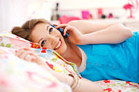 Smiling teenage girl talking on cell phone in bedroom