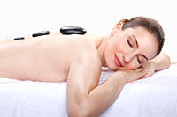 Woman having a hot stone treatment, smiling, eyes closed
