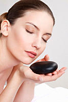 Close up of woman with hot stone, eyes closed