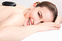 Woman having a hot stone treatment, smiling, portrait (thumbnail)