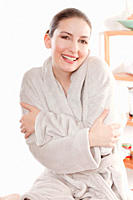 Woman in bathrobe with arms crossed, smiling, portrait (thumbnail)