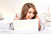 Woman lying on bed with laptop and showing thumbs up