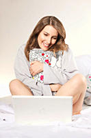 Woman sitting on bed holding pillow and with laptop