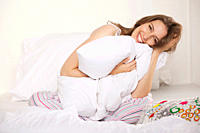 Woman sitting on bed and holding pillow, smiling