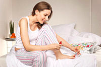 Woman sitting on bed and applying nail varnish