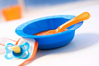 Baby food in bowl with pacifier