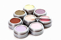 Multi coloured eye shadows with make up brush on white background