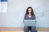 Germany, Leipzig, Young woman sitting and using laptop, smiling