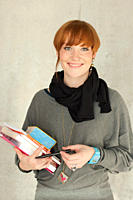 Germany, Leipzig, Young woman standing with books, smiling, portrait