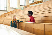 Germany, Leipzig, Students sitting face to face and talking in auditorium