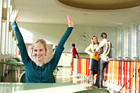 Germany, Leipzig, Woman sitting and raising hands in hallway, students standing in background