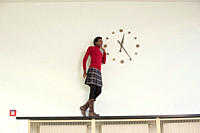 Germany, Leipzig, University student standing and looking at wall clock