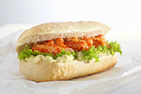Baguette roll filled with crayfish against white background.