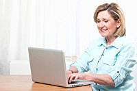 Woman using laptop, smiling