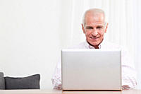Man using laptop, smiling