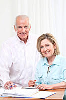 Senior couple doing paperwork, smiling, portrait