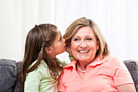 Girl 6_7 whispering into grandmother's ear, close_up