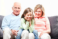 Granddaughter 6_7 sitting on lap of grandparents with head in hand, smiling, portrait