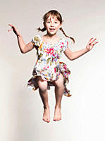 Girl 6_7 jumping against gray background, portrait, smiling