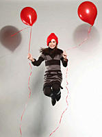 Girl 10_11 holding balloon and jumping
