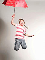 Girl 6-7 jumping with holding umbrella (thumbnail)