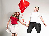 Children 10-13 holding balloons and jumping, smiling, portrait (thumbnail)