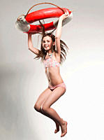 Girl 10-11 holding lifesaver and jumping, portrait, smiling (thumbnail)