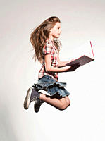 Girl 8_9 holding book and jumping, side view