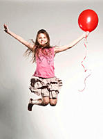 Girl 8_9 jumping with holding balloon, smiling, portrait