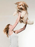 Teenage girl 16_17 lifting dog