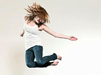 Teenage girl 16_17 jumping against gray background