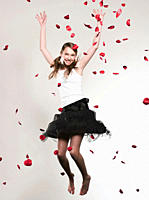 Girl 12_13 with arms up jumping, rose petals falling