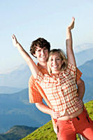 Young couple near mountain, arms up, portrait